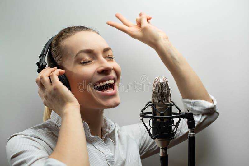 La muchacha hermosa joven escribe la pieza vocal, radio, voz superpuesta TV, lee la poesía, blog, hecho un podcast en estudio en  foto de archivo libre de regalías