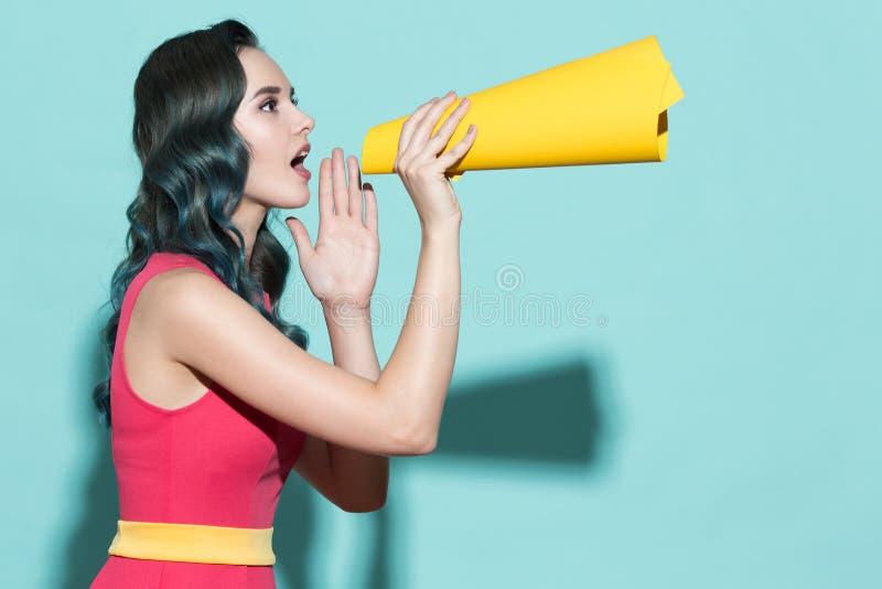 La muchacha hermosa joven habla en un altavoz de papel amarillo imagen de archivo libre de regalías