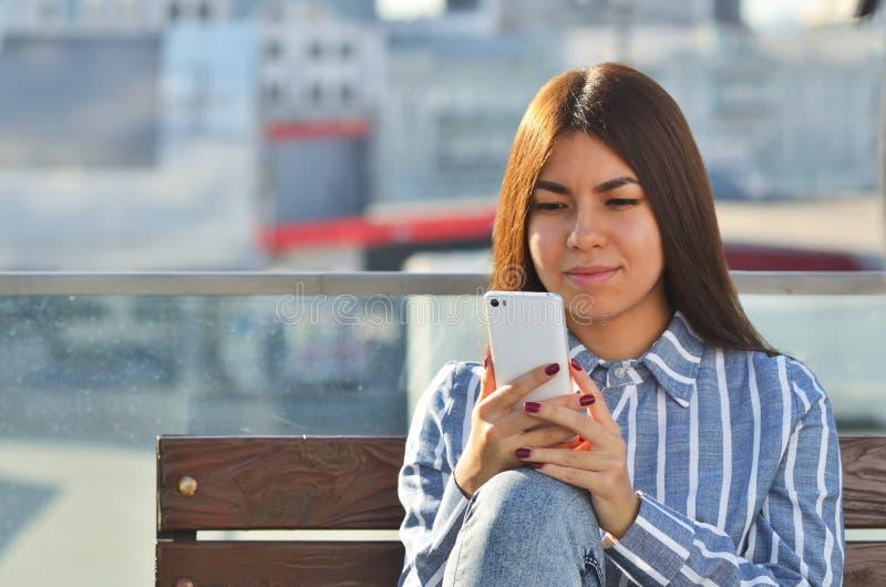 La muchacha hermosa joven hace el selfie y ella se está sentando en un banco en la ciudad imagenes de archivo