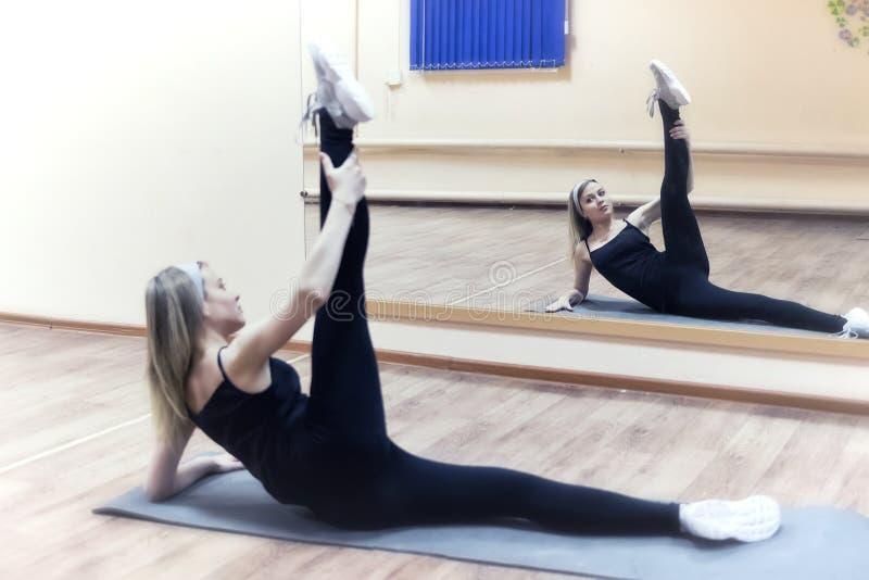 La muchacha hermosa joven hace estirar ejercicios delante del m fotos de archivo
