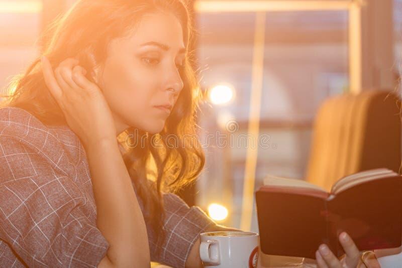 La muchacha hermosa joven mira el cuaderno y tiene conversación con los socios comerciales en el café imagen de archivo libre de regalías