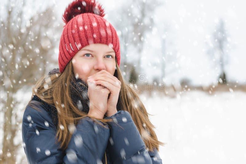 La muchacha hermosa joven respira en sus manos de modo que sea más caliente, debajo de nieve mullida suave en un día de invierno imagen de archivo libre de regalías