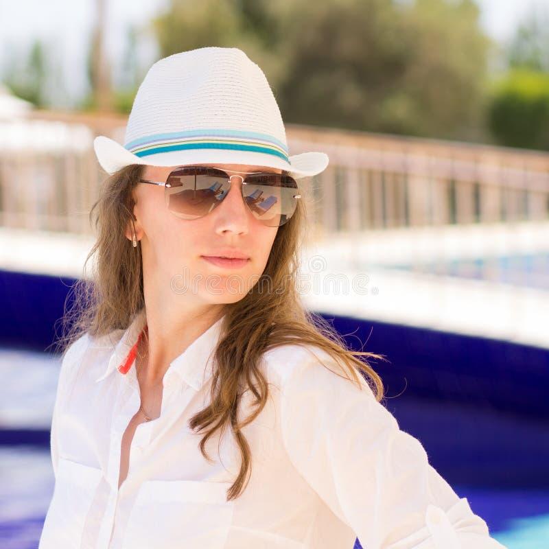 La muchacha hermosa joven se coloca cerca de la piscina imagen de archivo libre de regalías
