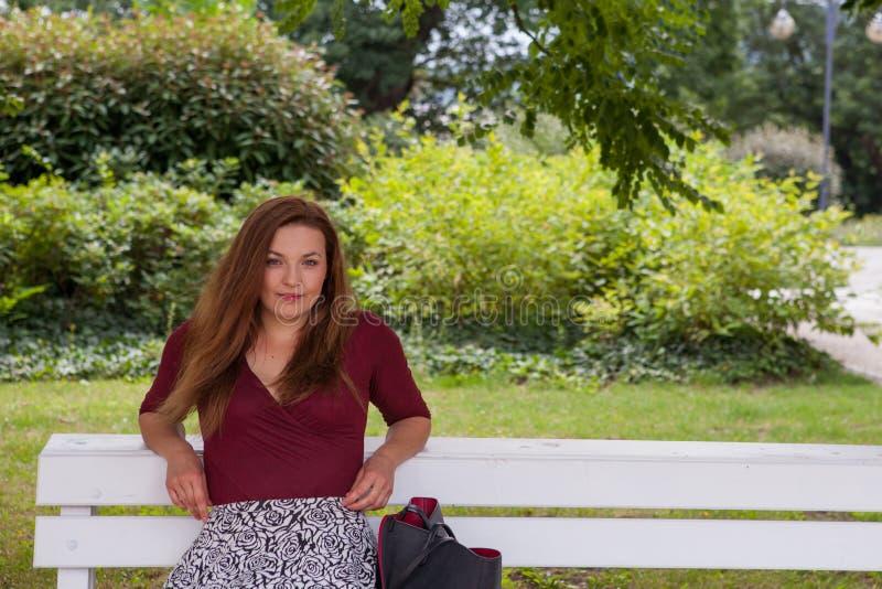 La muchacha hermosa joven se sienta en un banch imagen de archivo libre de regalías