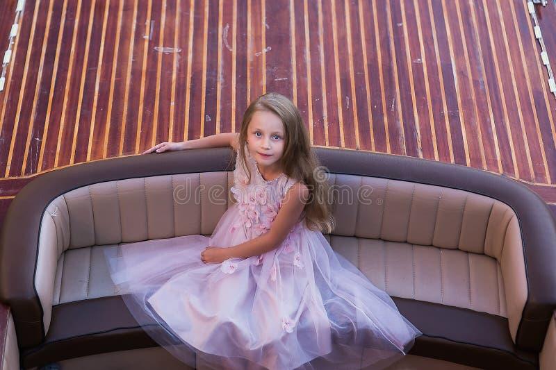 La muchacha hermosa linda con el pelo largo se sienta en el barco Princesa de la muchacha imagenes de archivo