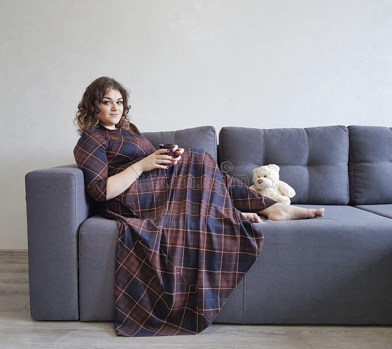 La muchacha hermosa llena de la sonrisa en el sofá se sienta con una taza imagen de archivo libre de regalías