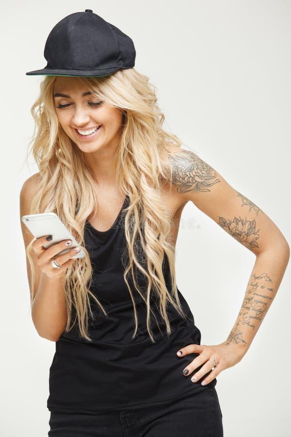 La muchacha hermosa mira el teléfono y risas sobre blanco aislada imagen de archivo