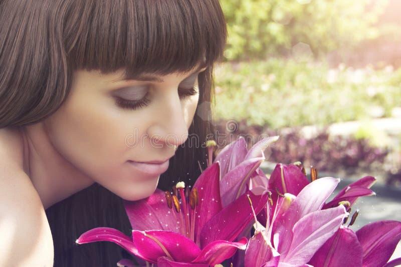 La muchacha hermosa mira el tono de las flores imagenes de archivo
