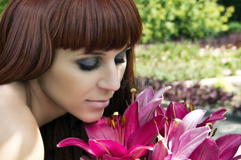 La muchacha hermosa mira las flores imagen de archivo libre de regalías