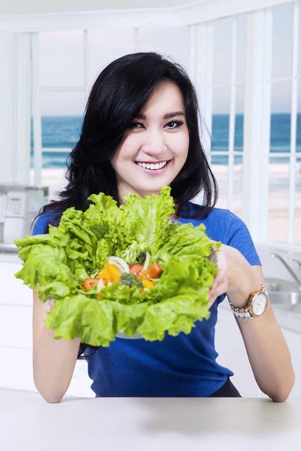 La muchacha hermosa muestra lechuga en la cocina imagen de archivo libre de regalías