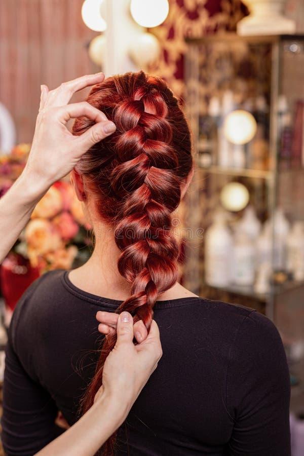 La muchacha hermosa, pelirroja con el pelo largo, peluquero teje una trenza francesa, en un sal?n de belleza Cuidado del cabello  imagenes de archivo