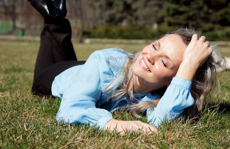 La muchacha hermosa que disfrutaba del día soleado, mintiendo en el césped con ella los ojos se cerró fotos de archivo
