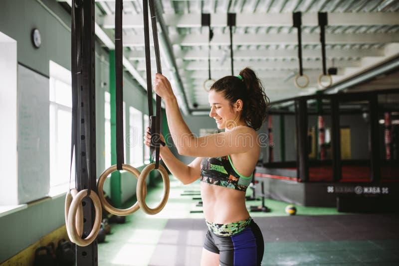 La muchacha hermosa que hace un ejercicio en el gimnasio suena en el gimnasio Feliz y sonrisa foto de archivo libre de regalías