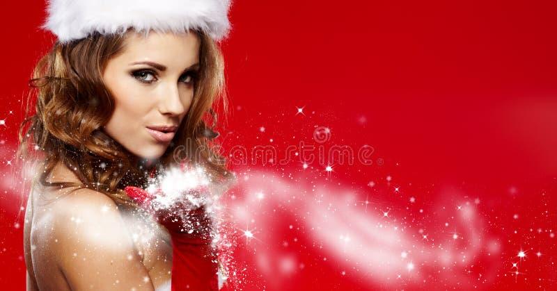 La muchacha hermosa que lleva a Papá Noel viste con la Navidad g imagenes de archivo