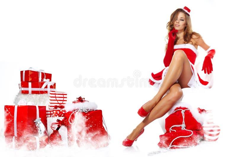 La muchacha hermosa que lleva a Papá Noel viste con la Navidad g imágenes de archivo libres de regalías