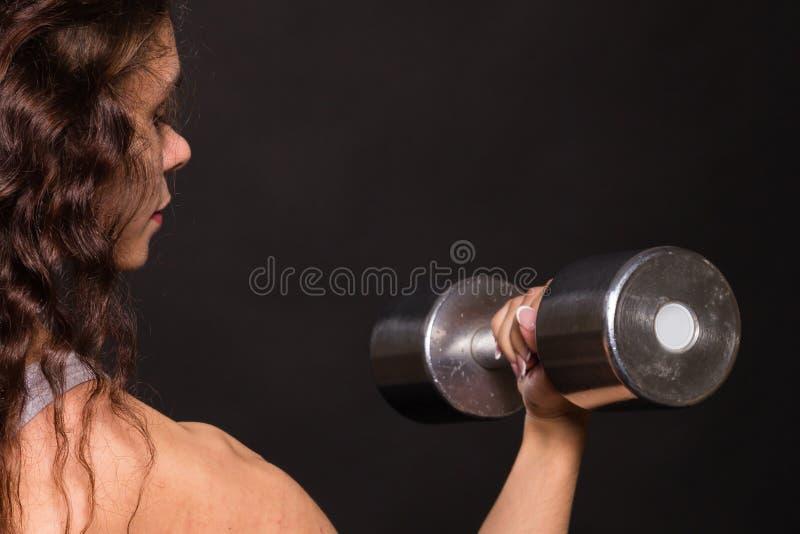 La muchacha hermosa que realiza deportes ejercita en un fondo oscuro foto de archivo libre de regalías