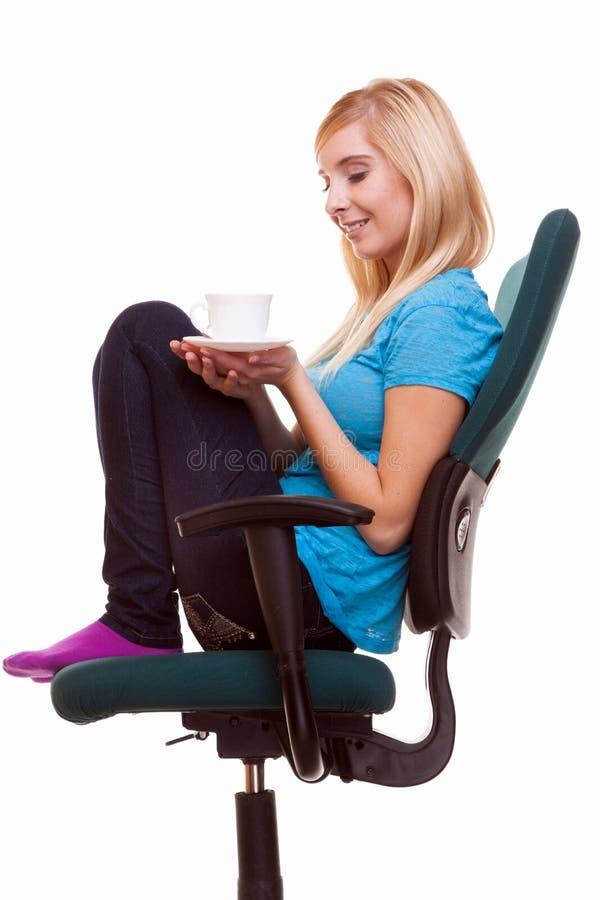 La muchacha hermosa que se relaja en silla sostiene una taza de té o de café fotos de archivo libres de regalías