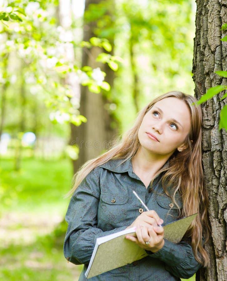 La muchacha hermosa romántica escribe los poemas del amor en la naturaleza imagen de archivo