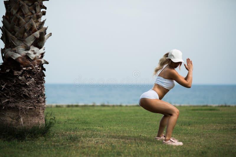 La muchacha hermosa se está resolviendo en parque del verano con una opinión sobre el mar foto de archivo libre de regalías