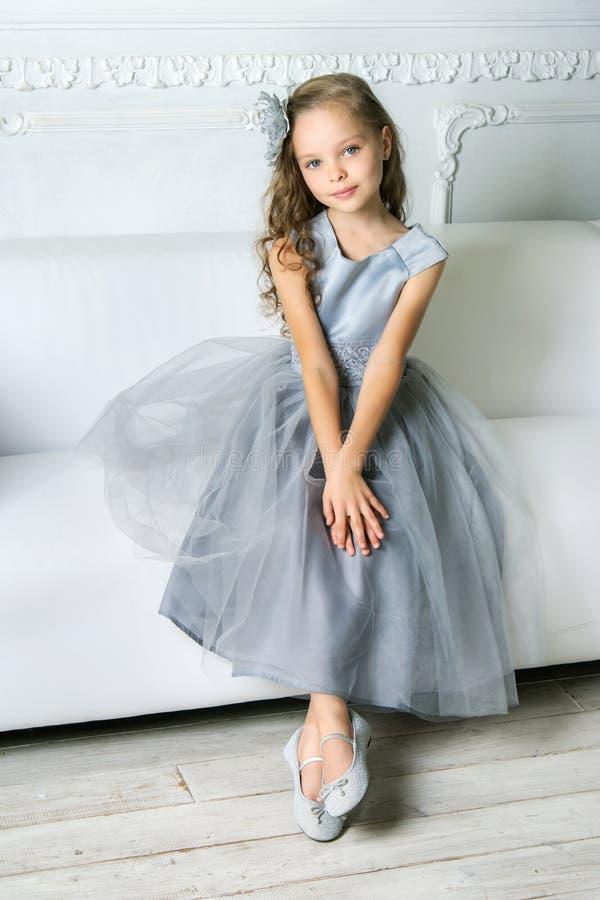 La muchacha hermosa se está sentando en el sofá fotografía de archivo libre de regalías