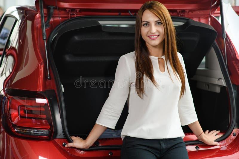 La muchacha hermosa se está sentando en el tronco de coche imagenes de archivo