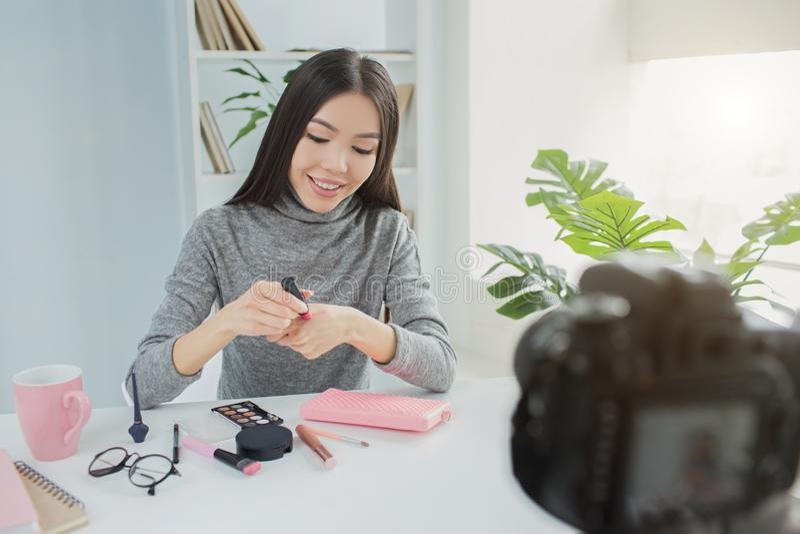 La muchacha hermosa se está sentando en la tabla y está haciendo un vídeo sobre sus productos de belleza del mes Ella está sosten fotos de archivo