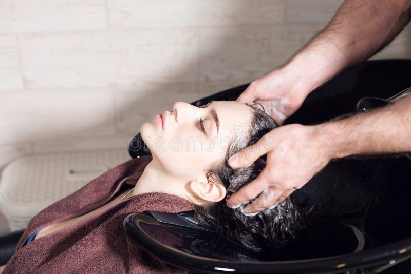 La muchacha hermosa se lava el pelo antes de un corte de pelo en un salón de belleza pelo que se lava en una peluquería, muchacha fotos de archivo