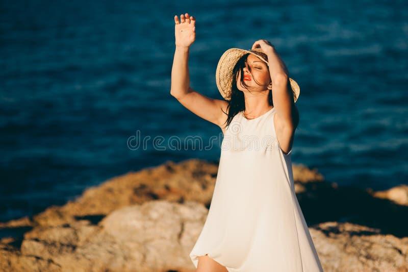 La muchacha hermosa se relaja en la roca en el mar de la costa foto de archivo libre de regalías