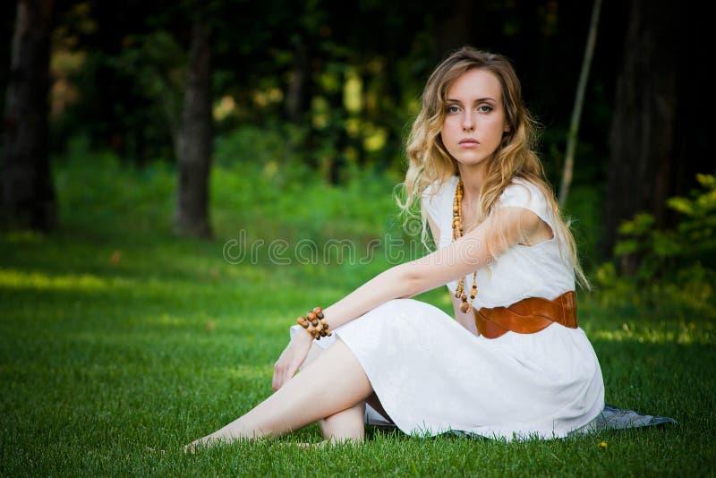 La muchacha hermosa se sienta en la hierba imagen de archivo libre de regalías