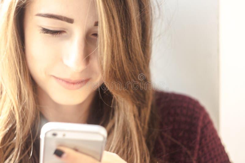 La muchacha hermosa sonríe y mira en el teléfono imagen de archivo libre de regalías