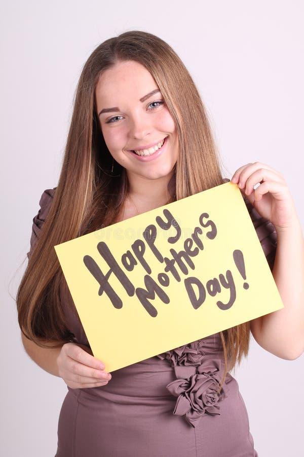 La muchacha hermosa sostiene una tabla con el día de madres feliz de las palabras imágenes de archivo libres de regalías