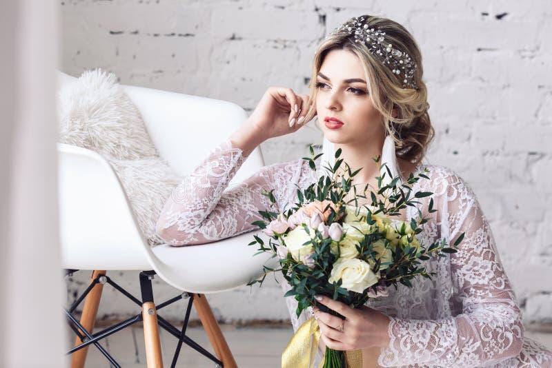 La muchacha hermosa vestida en peignoir y ropa interior se sienta en piso y sostiene el ramo en sus manos imágenes de archivo libres de regalías