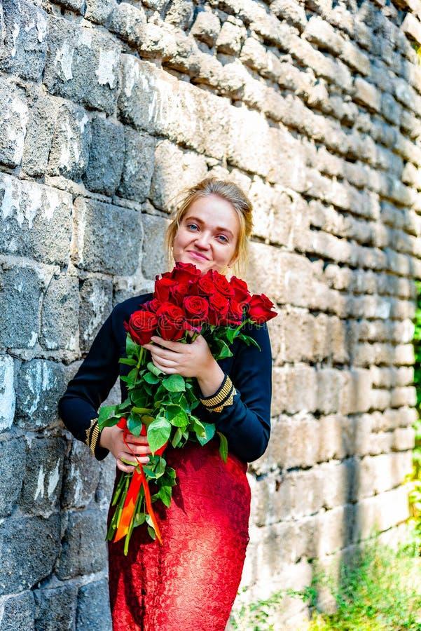 La muchacha hermosa y atractiva con un ramo de rosas rojas se coloca en el fondo de una pared de ladrillo vieja imagenes de archivo