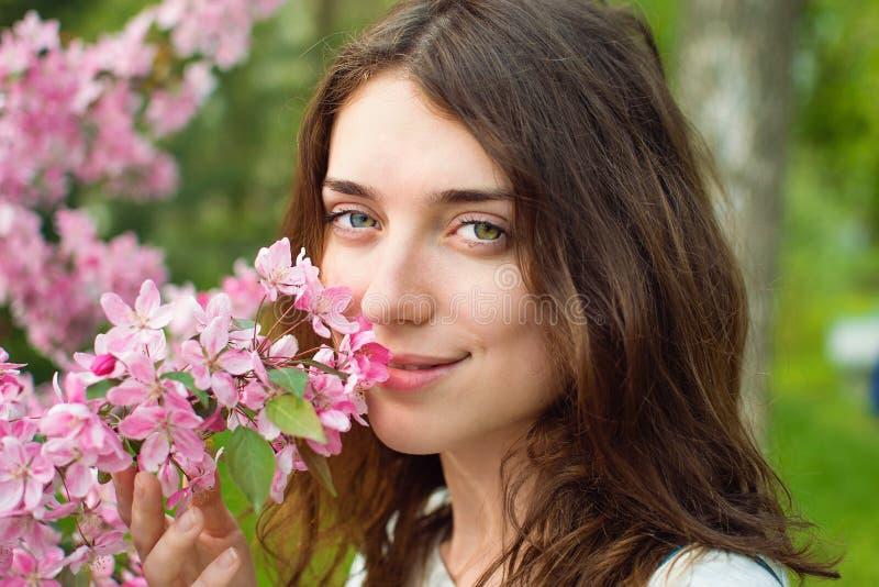 La muchacha huele una flor imagen de archivo