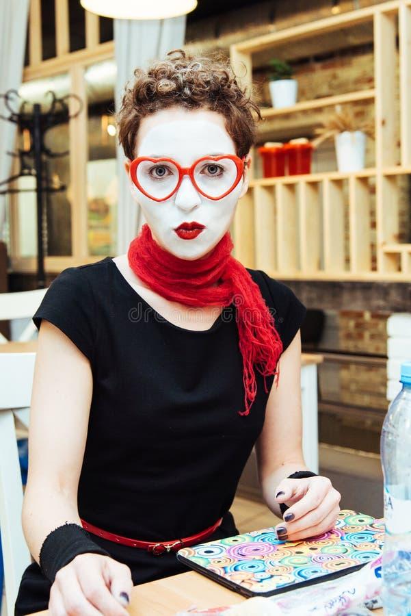 La muchacha imita sentarse en café y esperar una orden fotos de archivo