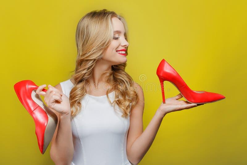 La muchacha impresionante y agradable está sosteniendo los zapatos rojos con los tacones altos en sus manos Ella está mirando uno imagen de archivo