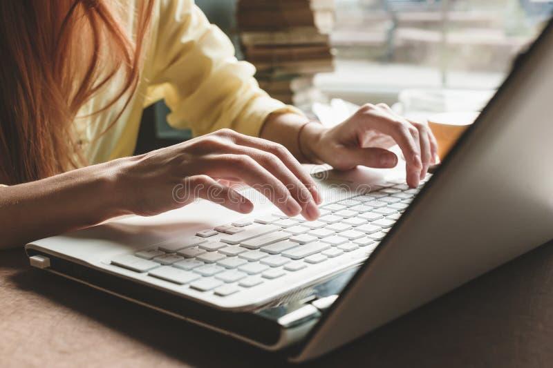 La muchacha imprime en un ordenador blanco Primer de manos en el teclado de un ordenador imagenes de archivo