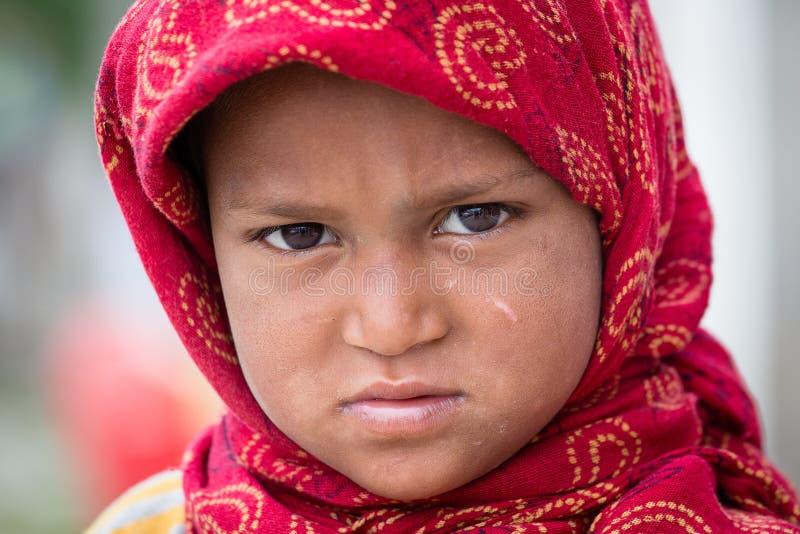 La muchacha india del mendigo pide dinero de un transeúnte en Srinagar, Cachemira La India foto de archivo