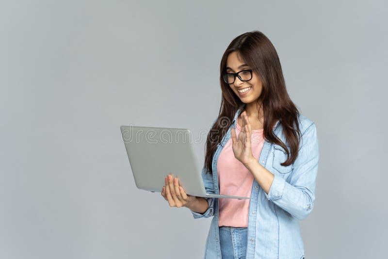 La muchacha india feliz que mira el ordenador portátil hace la llamada video aislado en fondo gris foto de archivo libre de regalías