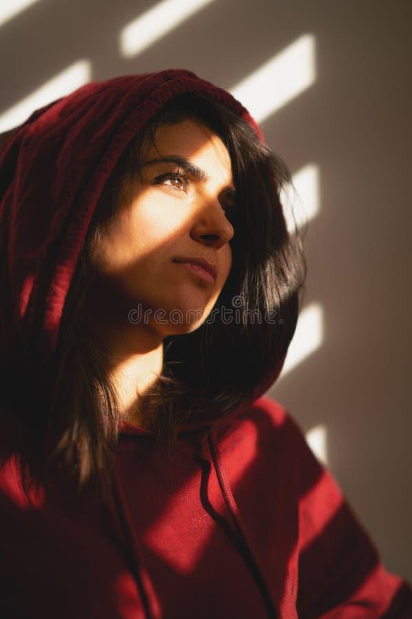 La muchacha infeliz se coloca sola en las persianas de ventana fotografía de archivo