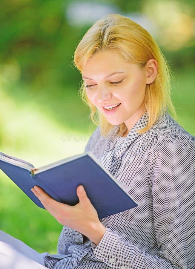 La muchacha interesada sienta el fondo leído parque de la naturaleza del libro Lectura de los libros inspiradores Literatura feme imágenes de archivo libres de regalías
