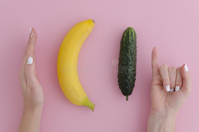 La muchacha jocosamente mide el tamaño de un plátano y de un pepino que comparan con el hombre largo o de gran tamaño En rosa fotografía de archivo