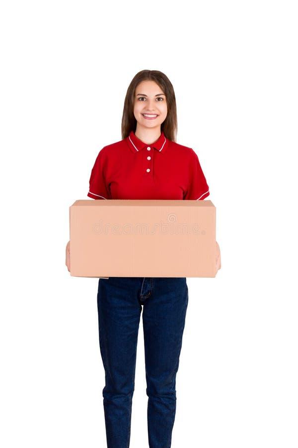La muchacha joven amistosa del delivey trae un paquete grande para un cliente aislado en el fondo blanco imagenes de archivo