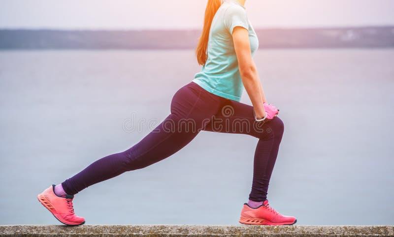 La muchacha joven, atractiva, atlética en los deportes se adapta, enganchado a mañana se divierte el entrenamiento fotografía de archivo