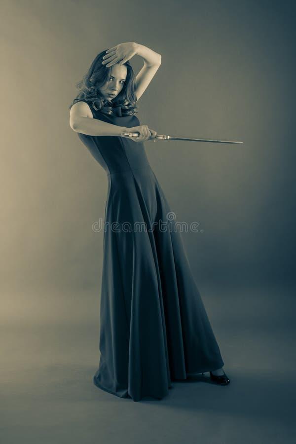 La muchacha joven atractiva de la princesa se defiende con una espada foto de archivo libre de regalías