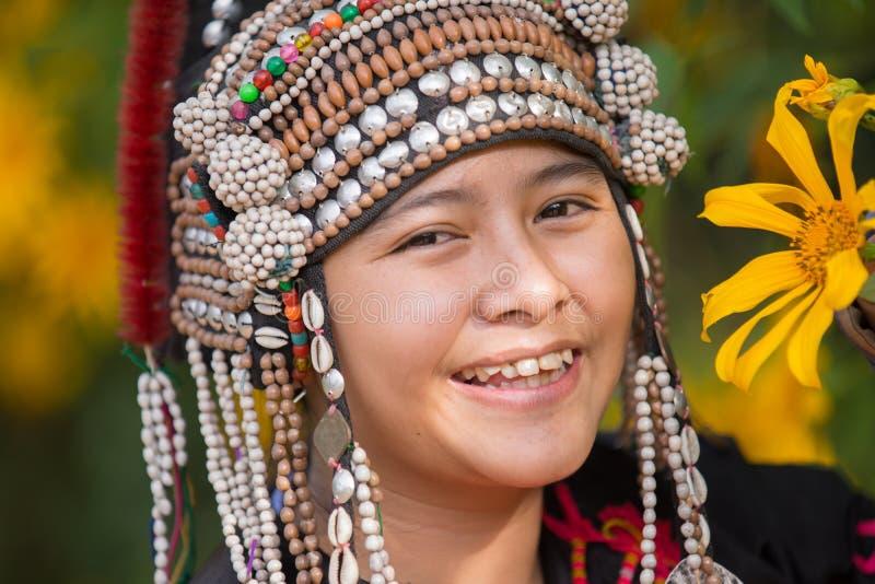 La muchacha joven de la tribu de la colina de la sonrisa hermosa en girasoles cultiva un huerto fotografía de archivo