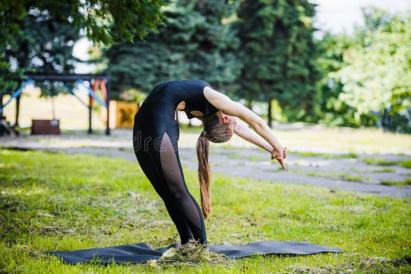 La muchacha joven del deporte hace la yoga en el parque, mujer asiática de la belleza fotografía de archivo libre de regalías