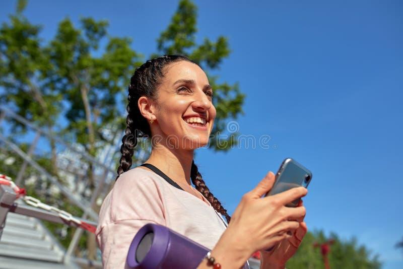 La muchacha joven del inconformista está charlando vía el teléfono móvil en red con sus amigos y el escuchar la música, bastante  foto de archivo