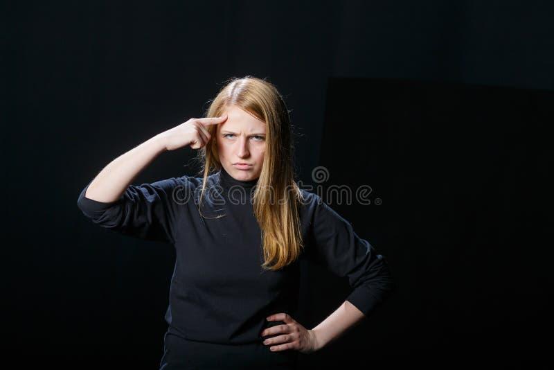 La muchacha joven del pelo rubio aumentó su finger a su cabeza contra foto de archivo libre de regalías