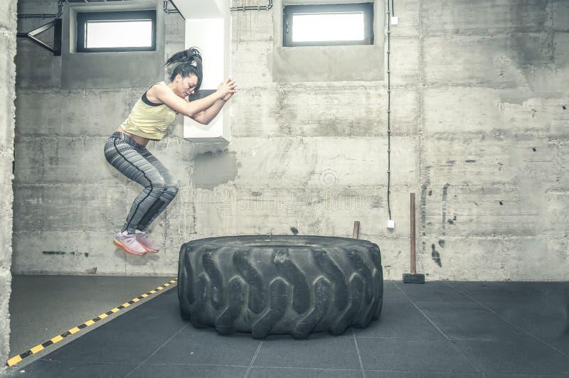 La muchacha joven y atractiva hermosa de la aptitud salta en el neumático del tractor como entrenamiento duro en el gimnasio, ima fotos de archivo libres de regalías